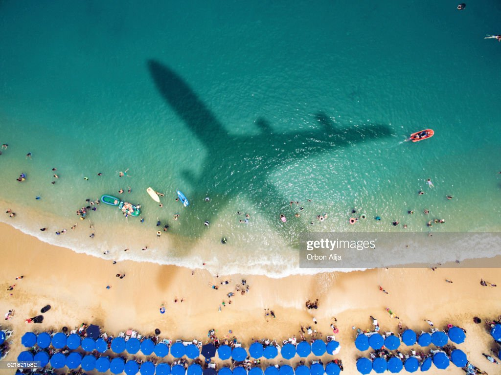 Airplane's shadow over a crowded beach : Stock Photo