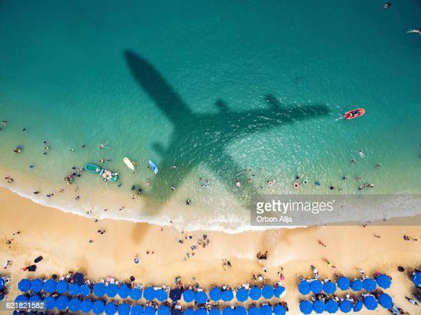 airplane's shadow over a crowded beach - toerisme stockfoto's en -beelden