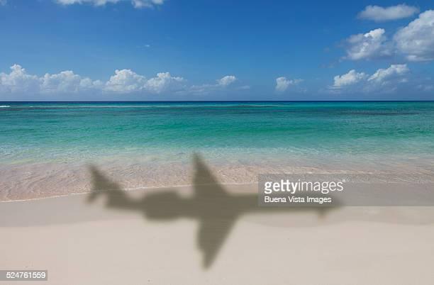 airplane's shadow over a tropical beach