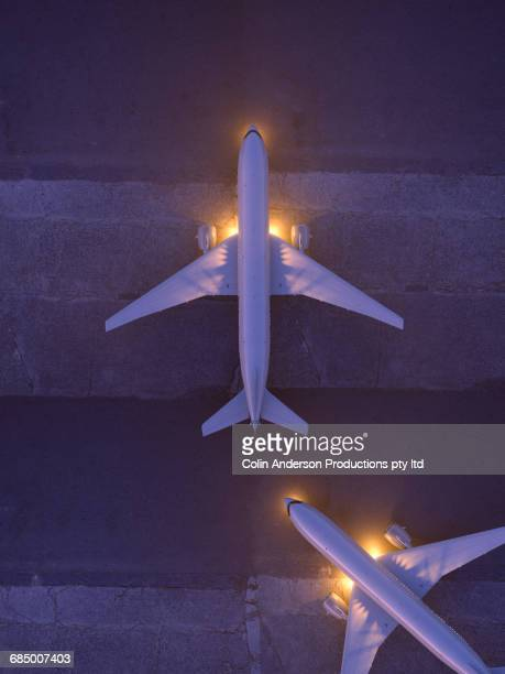 Airplanes taxiing on runway at night