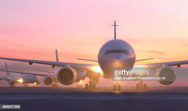 airplanes taxiing on runway at sunset - airport runway stock pictures, royalty-free photos & images