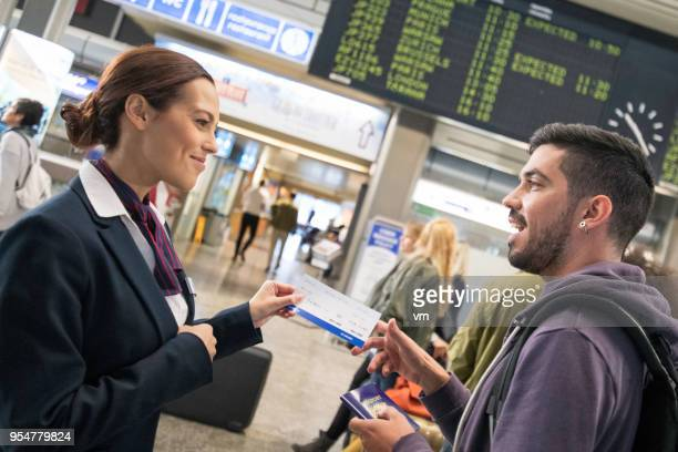 Airport attendant helping young hispanic man