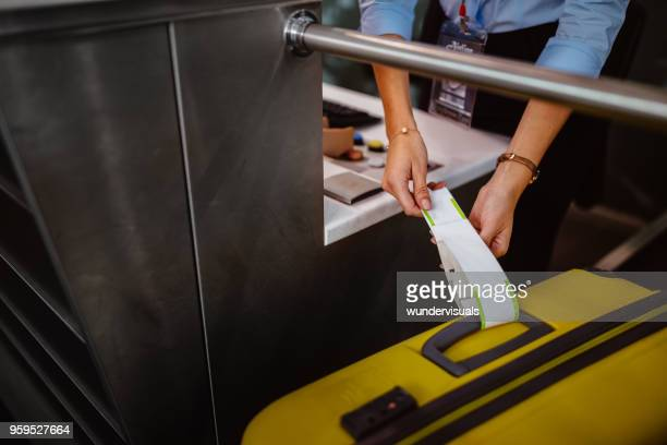 Airport check-in counter employee attaching tag on luggage