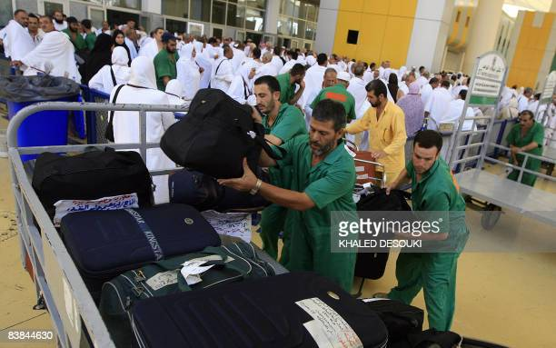 Airport employees load a cart with the suitcases of Muslim pilgrims upon their arrival to King Abdul Aziz airport in the Red Sea port city of Jeddah...