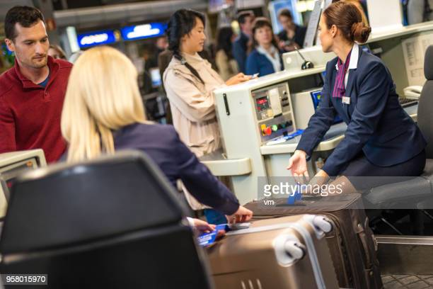 Airport employees marking luggage