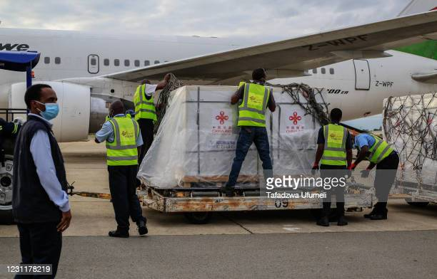 Airport employees unseal a shipment of Sinopharm Covid-19 vaccine at the Harare International Airport on February 15, 2021 in Harare, Zimbabwe. The...