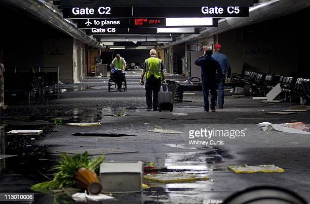 Airport employees walk past debris on Concourse C at Lambert International Airport's Terminal One after an apparent tornado caused extensive damage...
