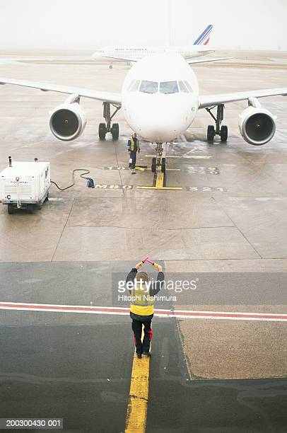 Airport ground crew directing aircraft, elevated view