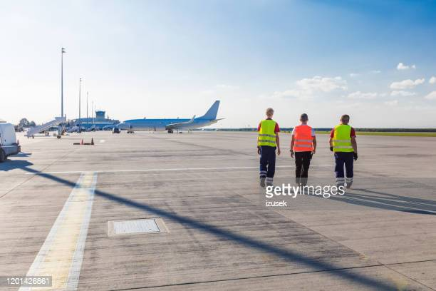 airport ground crew walking on the runway, back view - airfield stock pictures, royalty-free photos & images