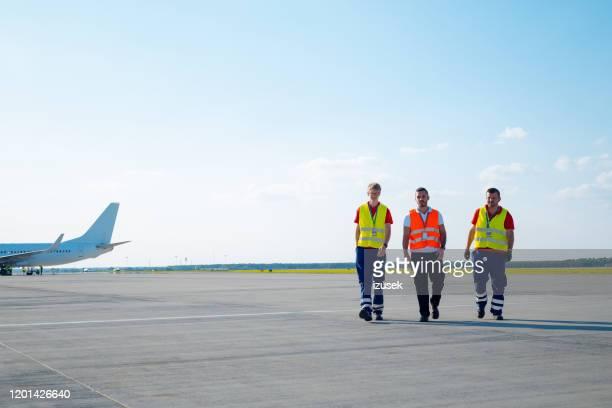 de grondbemanning die van de luchthaven op de baan loopt - izusek stockfoto's en -beelden
