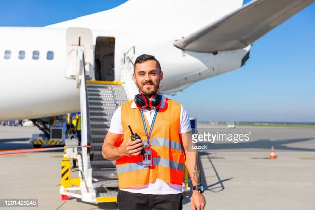 airport ground service man in front of airplane - employee stock pictures, royalty-free photos & images