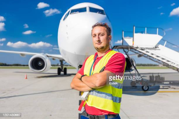 airport ground service, young man in front of aircraft - izusek stock pictures, royalty-free photos & images