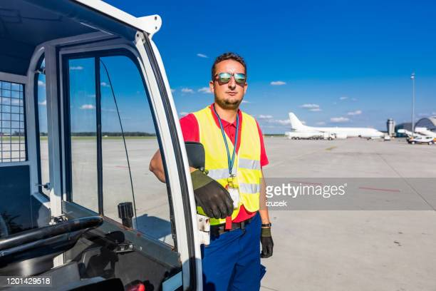 de gronddienst van de luchthaven jonge mens die zich op de baan bevindt - crew stockfoto's en -beelden