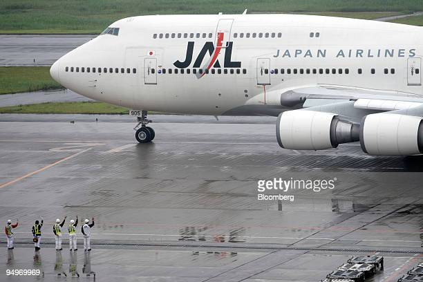 Airport ground staff monitor a Japan Airlines Corp airplane at Haneda Airport in Tokyo Japan on Tuesday July 21 2009 American Airlines the world's...