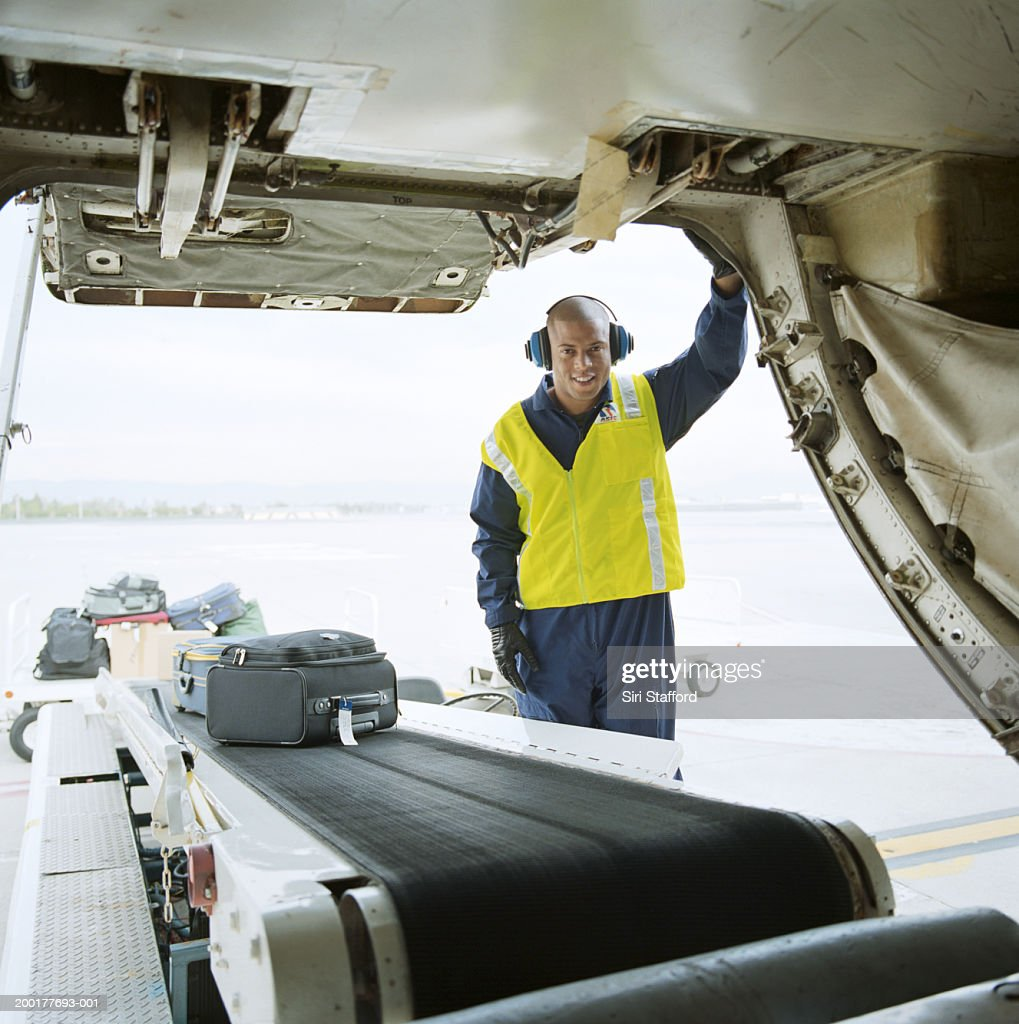 Airport ground technician loading luggages into cargo hold of aircraft : Stock Photo