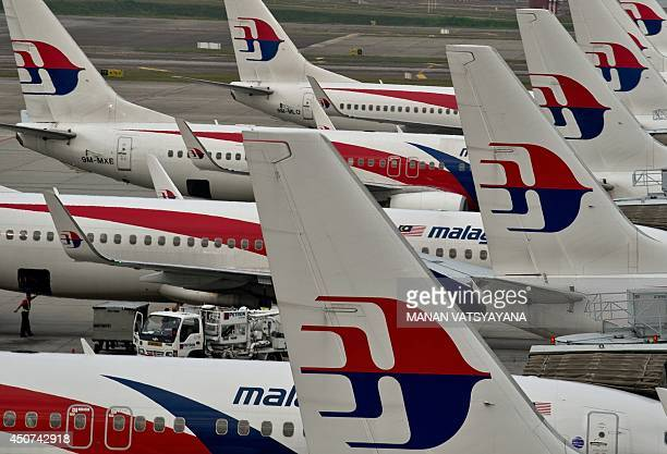 Airport groundstaff walk past Malaysia Airlines planes parked on the tarmac at the Kuala Lumpur International Airport in Sepang on June 17 2014...