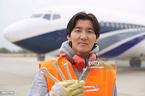 Airport hangar worker on tarmac with wrenches
