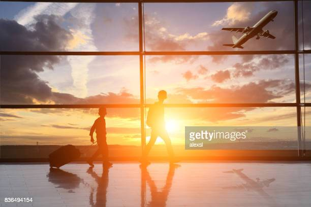 Airport interior child travel silhouette sunset
