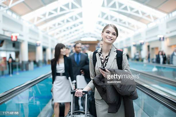 Airport Moving Walkway with Smiling Businesswoman Holding Cell, Copy Space