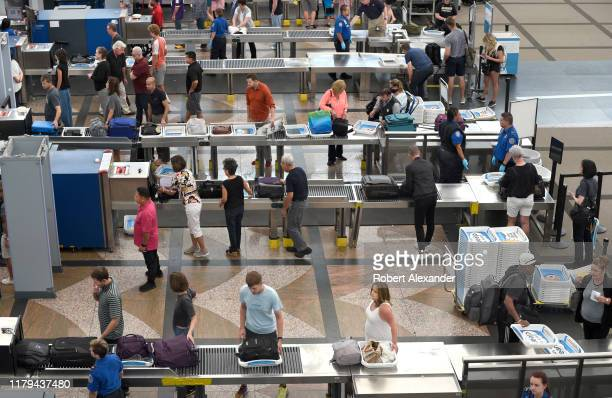 Airport passengers proceed through the TSA security checkpoint at Denver International Airport in Denver, Colorado.