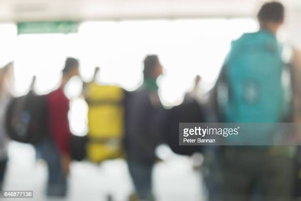 Airport passengers with backpacks wait at counter to board airplane, brightly lit, defocussed