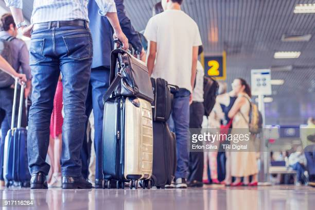 airport people waiting in the line - wachten stockfoto's en -beelden