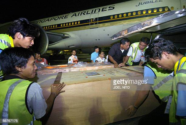 Airport personell lift the crate containing the remains of Filipina maid Jane la Puebla whose body was found chopped and scattered in Singapore on...
