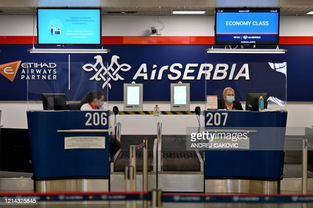 Airport personnel wearing protective face masks wait for passengers behind plexiglas at the check-in counters at the Belgrade's airport on May 21 as...