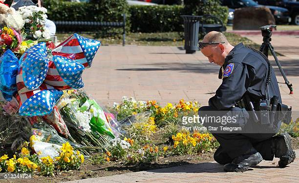 Airport police officer kneels at the growing memorial at the Euless Police Headquarters on March 2 2016 in Euliss Texas Citizens and the Euless...