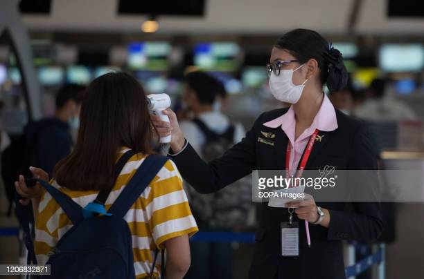 Airport receptionist wearing a face mask as a protective measure against the corona virus checks the body temperature a tourist at Suvarnabhumi...