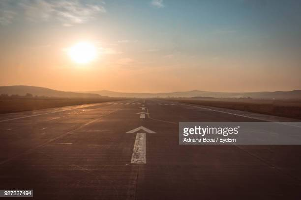 airport runway against sky during sunset - airport runway stock pictures, royalty-free photos & images