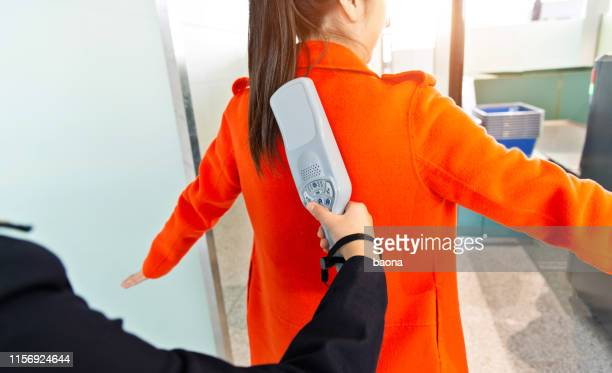 airport security check using a metal detector on a passenger - metal detector security stock pictures, royalty-free photos & images