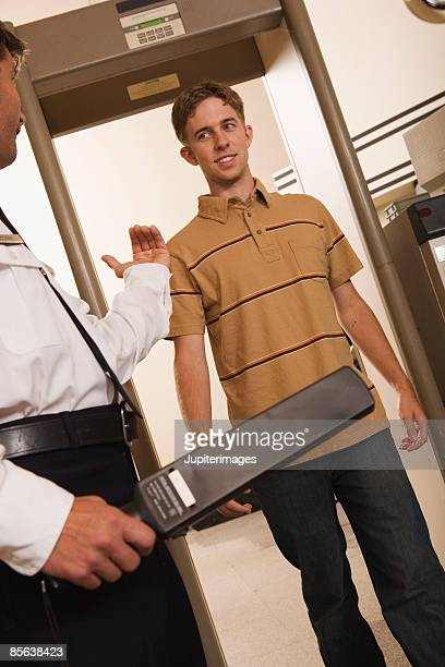 Airport security officer directing man through security checkpoint