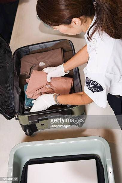 airport security officer inspecting luggage - security check stock photos and pictures