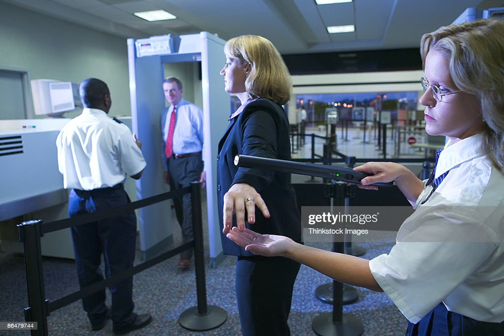 Airport security officer searching woman : Foto de stock