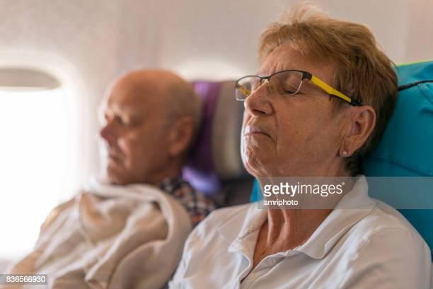 Airport, senior couple sleeping in airplane
