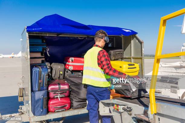 airport service crew unloading luggage - izusek stock pictures, royalty-free photos & images