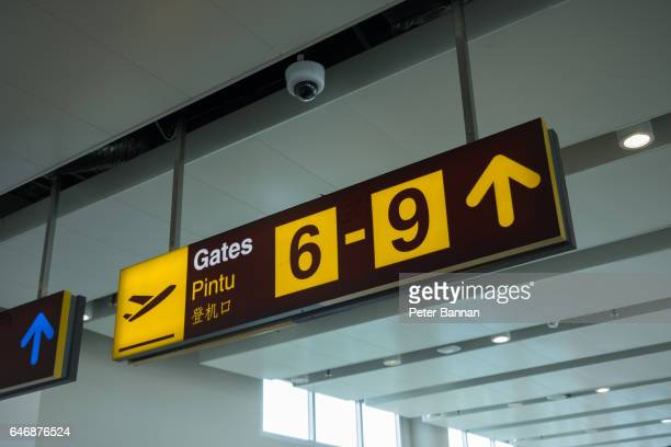 Airport signage to gate, suspended, illuminated yellow, at airport, Bali