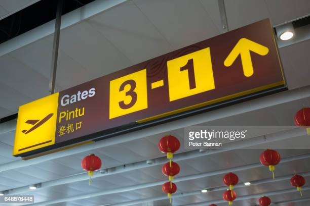 Airport signage to gate, suspended, illuminated yellow, Bali Indonesia