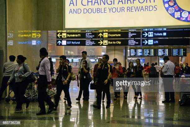 Airport staff are evacuated from the departure terminal of Changi Airport Terminal 2 after smoke filled the airport in Singapore on May 16 2017...