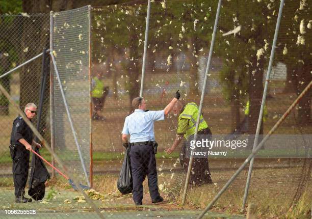 Airport staff clean insulation from a fence after the airport hangar roof that was ripped off in a storm that hit Canberra on November 2 2018 in...