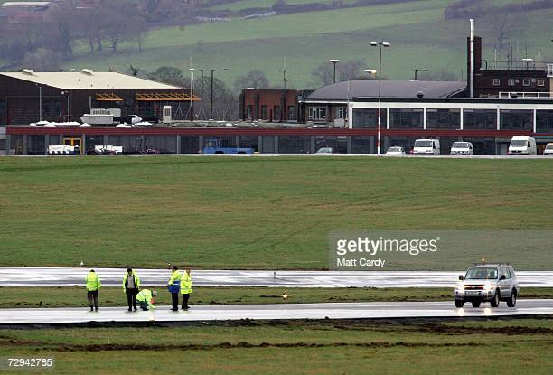 Airport staff inspect the runway after numerous airlines refused to land or take off after safety fears at Bristol International Airport January 7...