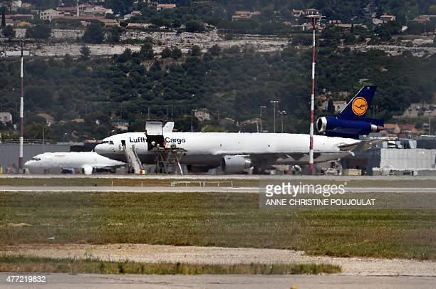 Airport staff load coffins bearing the remains of Spanish victims of the Germanwings flight crash onto a Lufthansa cargo plane on June 15, 2015 at...