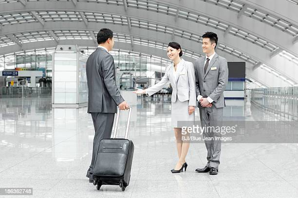 Airport staff members welcoming passenger in airport lobby