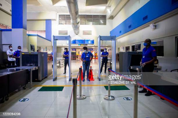 Airport staff stand at a security checkpoint at Toussaint Louverture International Airport on June 26, 2020 in Port-au-prince, Haiti. - After more...