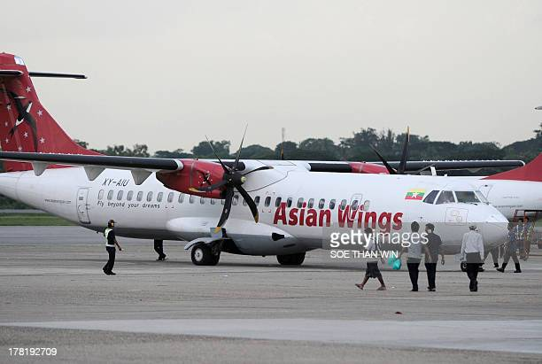 Airport staff walk by an Asian Wings aircraft at Yangon's international airport on August 27 2013 Japan's All Nippon Airways said on August 27 it...