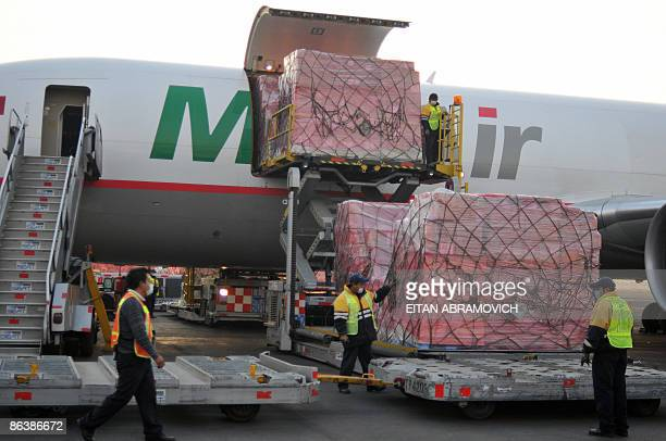 Airport staffers wearing face masks unload humanitarian aid sent by South Korea upon its arrival at Benito Juarez International airport in Mexico...