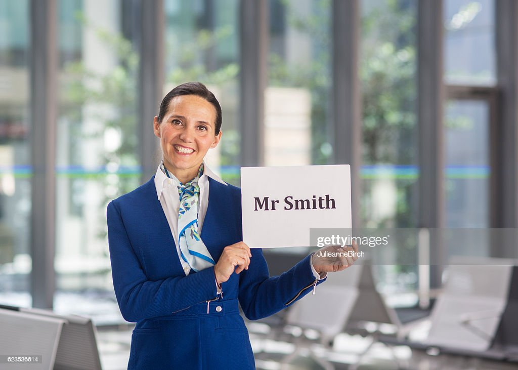Airport stewardess to welcome Mr Smith : Stock Photo