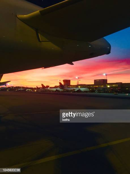 Airport tarmac with a dramatic sunset sky.