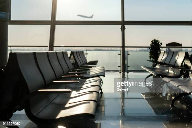 airport waiting area against airplane taking off - gate stock pictures, royalty-free photos & images